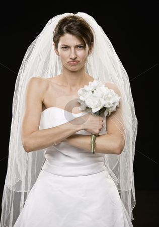 Young Woman in Wedding Dress stock photo, Young woman in wedding dress and veil frowning.  Vertically framed shot. by Jonathan Ross