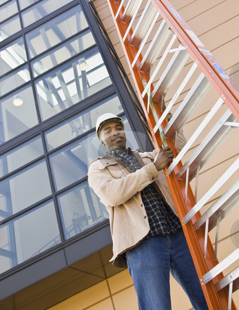 Male Construction Worker stock photo, Male construction worker holding orange ladder.  Vertically framed shot. by Jonathan Ross