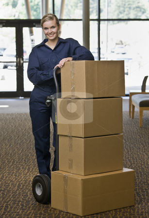 Young Woman Moving Boxes stock photo, Young woman using hand truck to move boxes.  Vertically framed shot. by Jonathan Ross