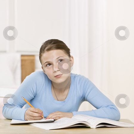 Young Girl Doing Homework stock photo, Young girl sitting at table doing homework.  Square framed shot. by Jonathan Ross
