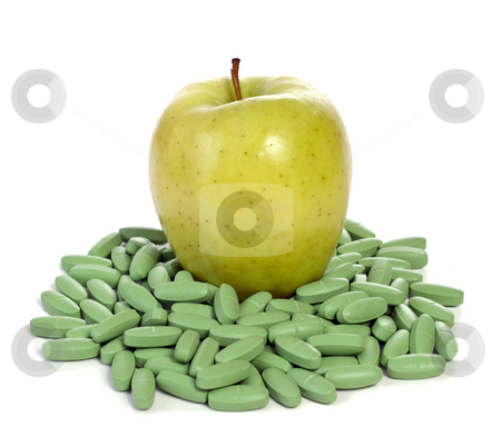 Healthy Food stock photo, Concept image of an apple sitting on a bunch of vitamins to show that this fruit is full of nutrients by Richard Nelson