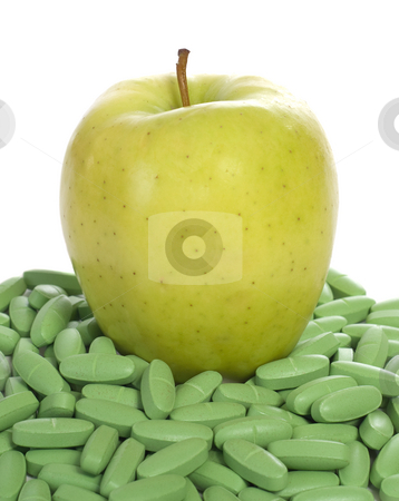 Nutrition stock photo, Concept image of an apple sitting on a bunch of vitamins to show that this fruit is full of nutrients by Richard Nelson