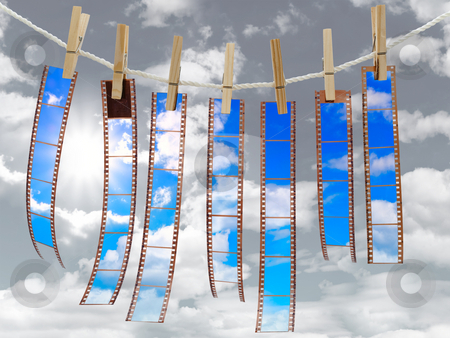 Film reel  stock photo, Colored films at the pegs against the cloudy sky by Sergej Razvodovskij