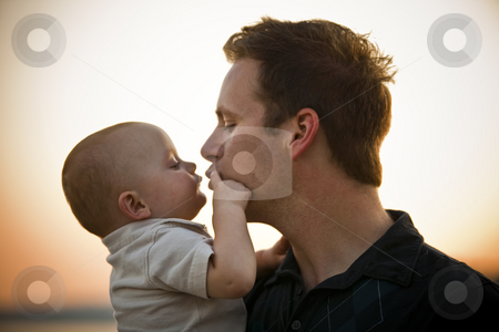 Father Kissing Baby stock photo, Father and baby at sunset, with father about to kiss baby. Horizontal. by Keith Brofsky