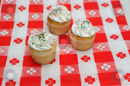 Three Cupcakes stock photo, White cupcake with light colored frosting on a red and white tablecloth by Lynn Bendickson