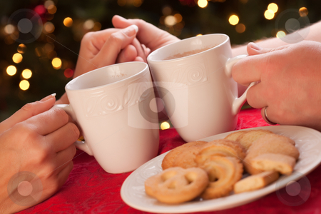 Man and Woman Sharing Hot Chocolate and Cookies stock photo, Man and Woman Sharing Hot Chocolate and Cookies in Front of Holiday Lights. by Andy Dean