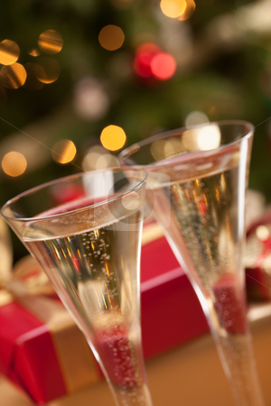 Sparkling Champagne Flutes and Gifts stock photo, Sparkling Champagne Flutes and Gifts in Front of Decorations and Lights. by Andy Dean