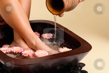 Soothing foot soak stock photo, Water pouring from an earthenware pot into a luxurious aromatic foot soak by Leah-Anne Thompson