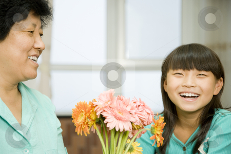 Grandmother and Granddaughter Laughing stock photo, A woman and her granddaughter laugh together near a bouquet of flowers.  They are looking away from the camera.  Horizontally framed shot. by Paul Burns