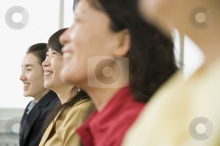 Side View of Four Women of Varying Ages stock photo, Cropped image of four women of varying ages. They are all smiling, looking away from the camera, head and shoulders viewable and in profile. Horizontally framed shot. by Paul Burns