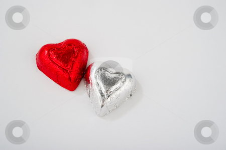 Two Foil Wrapped Heart Shaped Candies stock photo, Image of two foil wrapped heart shaped candies by Greg Blomberg