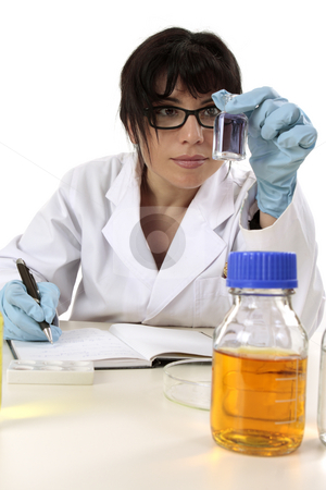 Researcher at work stock photo, Female research scientist sitting at desk with laboratory research and documentation notes. by Leah-Anne Thompson