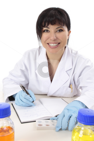 Smiling research scientist stock photo, Scientist at desk with research notes, spotting plate and laboratory chemicals. by Leah-Anne Thompson