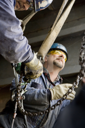 Two Male Construction Workers Rigging Lift stock photo, Two male construction workers wearing hardhats and sunglasses rigging lift. Vertical shot. by Paul Burns