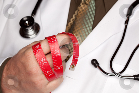 Doctor with Stethoscope Holding Measuring Tape stock photo, Doctor with Stethoscope Holding Red Measuring Tape. by Andy Dean