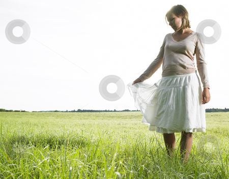 Woman in Field stock photo, Woman in field facing the camera, holding her skirt and looking at the ground. Horizontal shot. by Mog Ddl