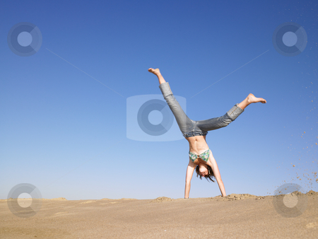 Woman Doing Cartwheel stock photo, Woman doing cartwheel in the sand. Horizontal shot. by Mog Ddl