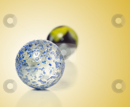 Marbles on Gold stock photo, Closeup view of a game of marbles shot on a white background with a slight reflection on the surface by Richard Nelson
