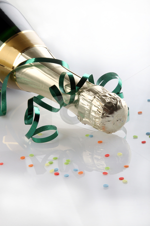Decorated wine bottle stock photo, Closeup of corked wine bottle decorated with ribbon and colorful confetti reflecting on white background. by Franz Schl?