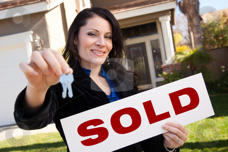 Hispanic Woman Holding Keys and Sold Sign In Front of House stock photo, Happy Attractive Hispanic Woman Holding Keys and Sold Sign In Front of House. by Andy Dean