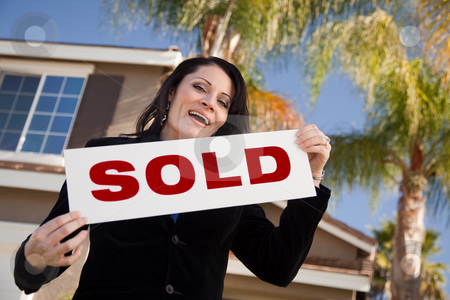 Attractive Hispanic Woman Holding Sold Sign In Front of House stock photo, Happy Attractive Hispanic Woman Holding Sold Sign In Front of House. by Andy Dean