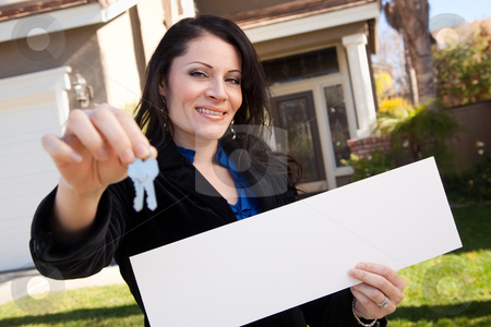 Attractive Hispanic Woman Holding Blank Sign in Front of House stock photo, Happy Attractive Hispanic Woman Holding Blank Sign and Keys in Front of House. by Andy Dean