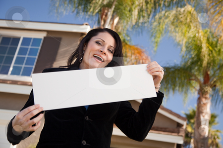 Attractive Hispanic Woman Holding Blank Sign in Front of House stock photo, Happy Attractive Hispanic Woman Holding Blank Sign in Front of House. by Andy Dean