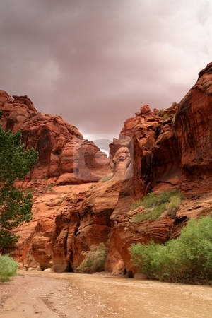 Storm clouds in the desert stock photo, Gray storm clouds hang over desert cliffs in southern Utah by Greg Peterson