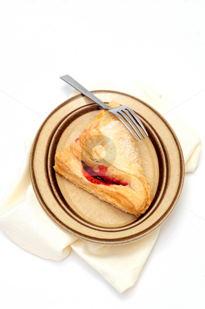 Cherry Turnover stock photo, A sweet Cherry Turnover with course ground sugar on top served on an oval brown colored saucer with a light colored cloth napkin under the plate by Lynn Bendickson