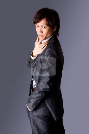 Successful Asian business man thinking stock photo, Successful Asian business man standing with confidence looking over his shoulder and one hand on chin and other in pocket, isolated. Corporate male with thinking expression. by Paul Hakimata