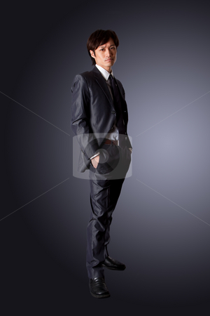 Successful Asian business man stock photo, Successful Asian business man standing with confidence and hands in pockets, isolated. by Paul Hakimata