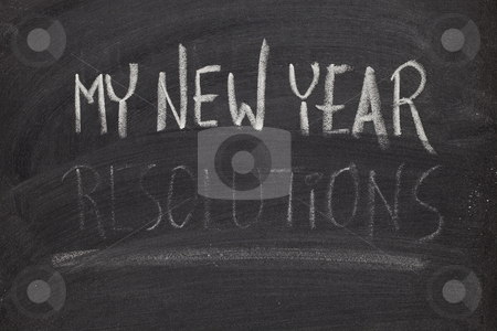 Forgetting new year resolutions - concept on blackboard stock photo, Concept of New Year resolution fading, being erased, forgotten or falling apart - white chalk handwriting on blackboard by Marek Uliasz