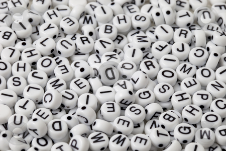 Alphabet background stock photo, White plastic beads with black letters placed randomly by Marek Uliasz