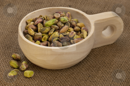 Scoop of raw shelled pistachio nuts stock photo, Raw shelled pistachio nuts on a rustic, wooden scoop with brown burlap background by Marek Uliasz