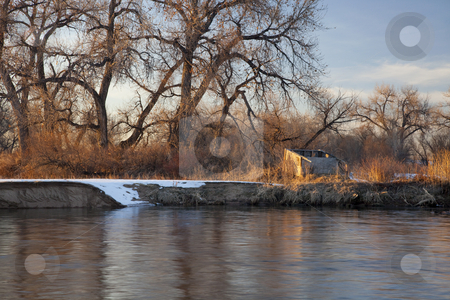 Blind for waterfowl hunting stock photo, Old blind for waterfowl hunting on shore of South Platte River, Colorado near Greeley, winter scenery with cottonwoods and some snow by Marek Uliasz