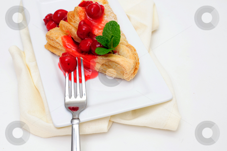 Cherry Turnover And Mint stock photo, Cherry Turnover with a topping of cherries and a red cherry sauce served on a white rectangular saucer and a light colored napkin by Lynn Bendickson