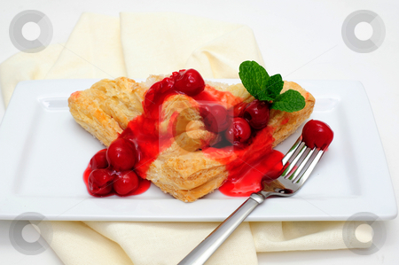 Turnover Topped With Cherries stock photo, Cherry Turnover with a topping of cherries and a red cherry sauce served on a white rectangular saucer and a light colored napkin by Lynn Bendickson