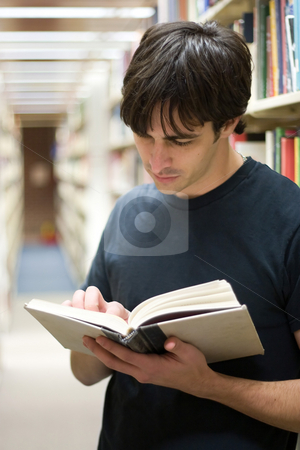 Student At the Library stock photo, A young man reads a book at the library while standing in the aisles of book shelves. by Todd Arena