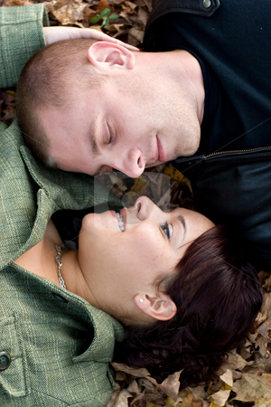 Young Couple In Love stock photo, A young happy couple passionately kissing each other while laying in some autumn leaves. by Todd Arena