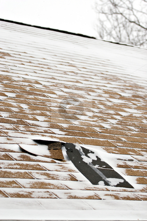 Winter Damaged Roof Shingles stock photo, Damaged roof shingles blown off a home from a windy winter storm with strong winds. by Todd Arena
