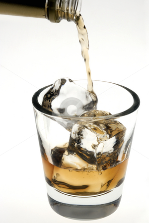 Whiskey being poured over ice cubes on a white background stock photo, Whiskey poured on the rocks in an empty old fashioned glass on a white background by Gabe Palmer