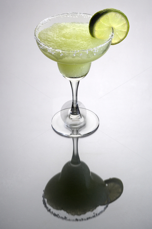 Frozen Margarita Cocktail stock photo, Frozen Margarita mixed drink with lime slice garnish on plain grey background with reflection by Gabe Palmer