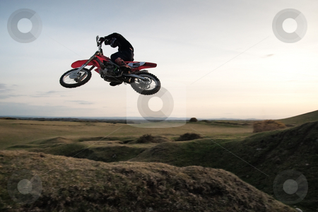 Motor cross rider stock photo, Motor cross rider jumping through the air by Viv Van der Holst