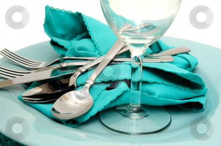 Turquoise Plate And Napkin stock photo, Turquoise colored dinner plate and cloth napkin with silverware including dinner and salad forks, soup and teaspoon, butter knife with a clear wine glass on top by Lynn Bendickson