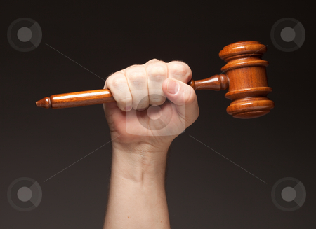 Male Fist Holding Wooden Gavel stock photo, Male Fist Holding Wooden Gavel on a Grey Background. by Andy Dean