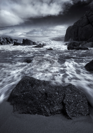 Holding back the Sea stock photo, A boulder holds backs the tides near Horseshoe Bay in South Australia by Mike Dawson