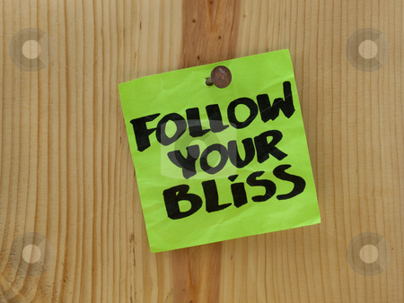 Follow your bliss - spiritual reminder stock photo, Follow your bliss handwriting on a green sticky note nailed to wooden wall or plank by Marek Uliasz