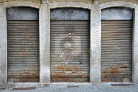 Lowered rolling shutters of a disused shop stock photo, Lowered rolling shutters of a disused shop, rusty, dirty and failure cityscape by Roberto Marinello