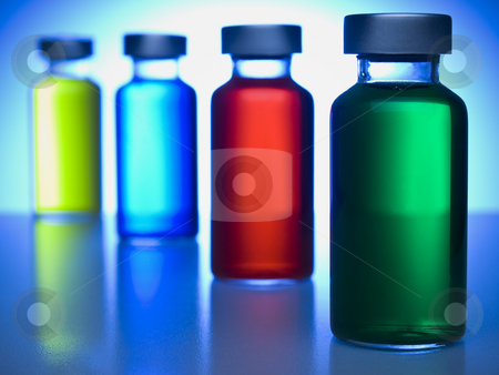 Row of vials stock photo, A row of vials filled with colored liquids. Focus on the green one. by Ignacio Gonzalez Prado