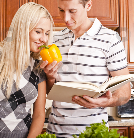 Young Woman Smelling Pepper Held by Young Man stock photo, Young man with cook book holding yellow pepper for young woman to smell. Vertical shot. by Christopher Nuzzaco